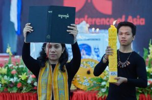 A woman holds the scriptures aloft as she processes into the plenary session during the opening session of the Asia Mission Conference in Yangon, Myanmar, on October 12, 2017.